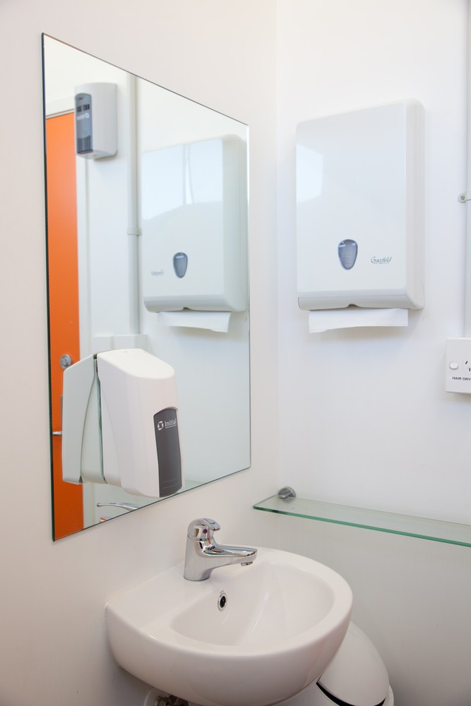 Private individual bathrooms which contain a shower, toilet, sink, mirror, power plug and bench